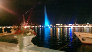 The jet d'eau illuminated in blue squirts water way up into the dark Geneva summer night sky.