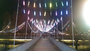 Colorful strips of light hanging over another foot bridge.